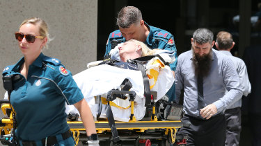 Julie Connor is taken by paramedics from the Federal Court in Brisbane, after having a medical episode, as her husband Peter (right) follows.