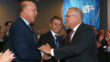 Prime Minister Scott Morrison pauses to shake hands with Home Affairs Peter Dutton at the QLD LNP convention.