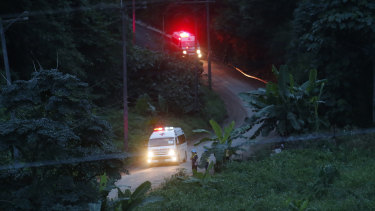 Two ambulances with flashing lights leave the cave area during the second phase of the rescue operation.