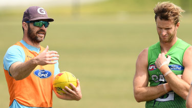 Matthew Scarlett (left) imparts some words of wisdom to Cats defender Lachie Henderson at training.