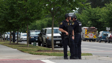 Virginia Beach Police Officers huddle near the intersection of Princess Anne Road and Nimmo Parkway following a shooting at the Virginia Beach Municipal Centre.