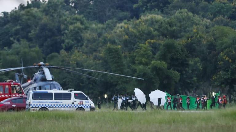 An emergency team rushes to a helicopter believed to be carrying one of the rescued boys from the flooded cave.