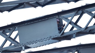 The man sits in a box in the framework of the Sydney Harbour Bridge as police negotiate with him.
