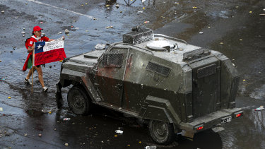 A demonstrator holds a Chilean flag toward an armoured police vehicle Chile's capital, Santiago, this week.