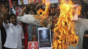 Members of a student  organisation shout slogans next to a burning effigy representing one of the men who is accused of the rape and murder of eight-year-old Asifa, during a protest in Bangalore, India, on Friday.