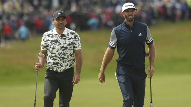 A step behind: Jason Day with Dustin Johnson of the United States at Royal Portrush.