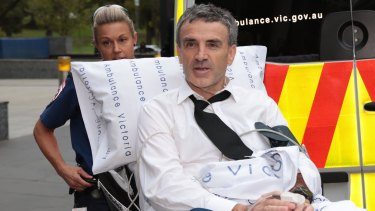 Dover Financial founder Terry McMaster leaves the Federal Court with the aid of paramedics after collapsing while being questioned at the royal commission.