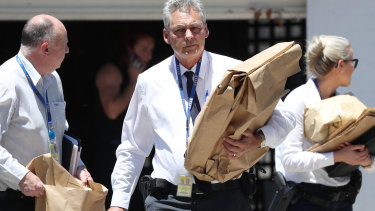 Homicide squad detectives leave the Altona home with bags of evidence.