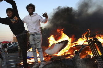Young men stand atop a burning car in the Target parking lot.