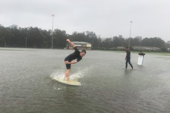 Kids have fun on their boards at flooded Nolan Reserve in Manly on Sunday.