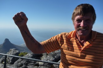 Jesper Jensen on top of Tabletop Mountain in South Africa, showing off a tattoo he dedicated to his late wife Gerri. He was due to go on the trip with her, but she died before they could go - he went with daughter Belinda instead.