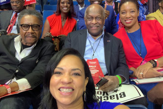 Herman Cain, centre, tweeted this photograph of himself at the Trump rally in Tulsa last month.