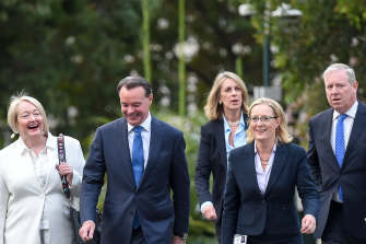 Opposition Leader Michael O'Brien walks into Tuesday's failed spill meeting flanked by supporters.