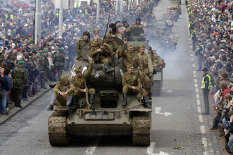 Soviet-made T-34 tanks with members of military history clubs dressed in the Red Army uniforms take part in a parade in Prague.