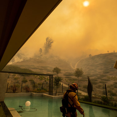 In California, an Orange County firefighter prepares to defend a home as the Silverado fire approaches a neighborhood in October 2020.