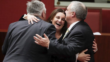 Jacqui Lambie celebrates with fellow crossbench senators Rex Patrick and Stirling Griff after the passage of the tax-cut bill on Thursday night.