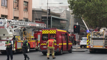 Firefighters and police at the fire on the corner of Russell and Bourke streets.