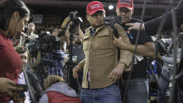A Trump supporter (centre) is restrained after he storms the media area where journalists including BBC reporter Gary O'Donoghue (second from left) were working.
