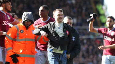 Paul Mitchell is led from the pitch by officials after his cowardly attack on Aston Villa's Jack Grealish.