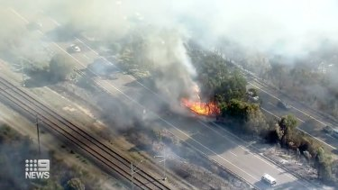 The fire is burning near train tracks, with buses replacing trains.
