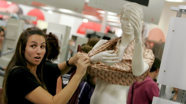 Sold like hotcakes ... a woman strips a mannequin for a Stella McCartney item at Target in 2007.