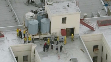 Firefighters and police officers on the Cecil Hotel roof in episode two of the series.