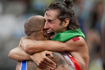 Tamberi embraces countryman Lamont Jacobs after the latter's stirring 100m triumph in Tokyo.
