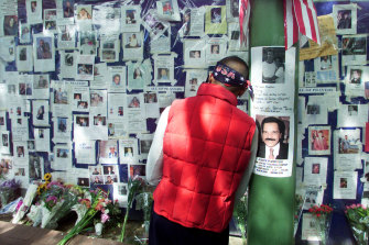 A man rests his head against a pole at Bellevue Hospital as he pauses in front of a wall of pictures of people missing in New York on September 15, 2001.  Relatives and friends of people missing as a result of the collapse of the World Trade Center are posting pictures on the wall.