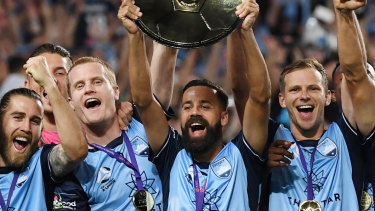 Sydney FC captain Alex Brosque lifts the A-League premiers plate with Alex Wilkinson to his right.