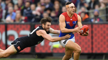 Daisy chain: Dale Thomas launches into tackle on Melbourne's Christian Petracca.