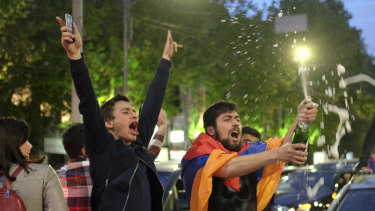 A man covered with a national flag waves an opened bottle of a sparkling wine celebrating Armenian Prime Minister's Serzh Sargsyan's resignation in Republic Square in Yerevan.