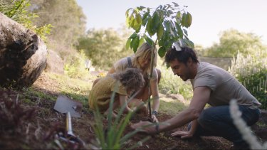 Filmmaker Damon Gameau planting a tree with his wife and daughter.