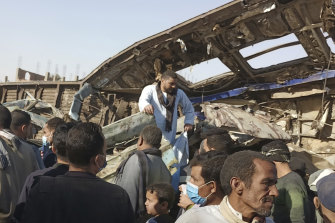 Villagers look for remains of victims around mangled train carriages at the scene of a train accident in Sohag,Egypt