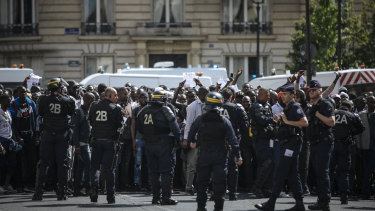 French police officers hold back protesters and migrants outside the Pantheon monument.
