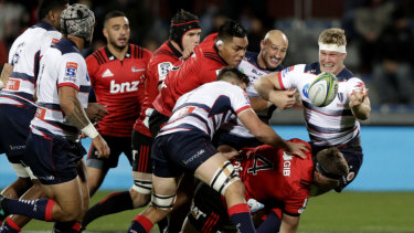 Crunched: Rebels' Matt Philip passes off under pressure against the Crusaders.