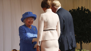 Queen Elizabeth II, left, smiles as she greets President Donald Trump and First Lady Melania Trump at Windsor Castle.