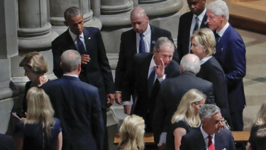 Former president George W. Bush, centre, leans in to talk to former vice-president Dick Cheney, as he walks out with, from left, former first lady Laura Bush, former president Barack Obama, former secretary of state Hillary Clinton and former president Bill Clinton, after attending the memorial service for Senator John McCain.
