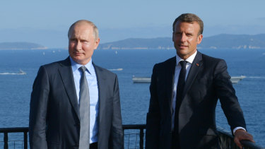 French President Emmanuel Macron, right, and Russian President Vladimir Putin pose for a photo during their meeting at the fort of Bregancon in Bormes-les-Mimosas, southern France, ahead of the G7 which Putin does not attend.
