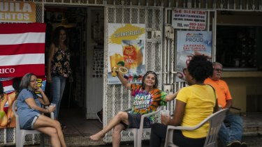 People drink beer on a patio before the arrival of Dorian in Boqueron, Puerto Rico.