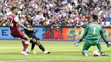 Bright start: Raheem Sterling guides the ball past West Ham goalkeeper Lukasz Fabianski for City's second goal at London Stadium.
