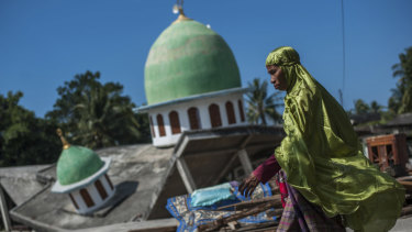 A Muslim woman walks past a mosque that collapsed after the earthquake in Gangga, Lombok Island.