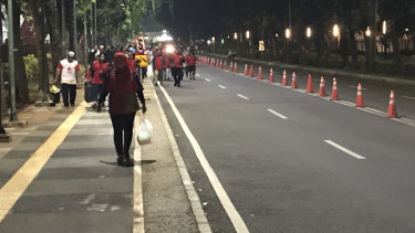 Locals, fearing a bomb attack, leave the Gelora Bung Karno Stadium complex in Jakarta on Sunday night.