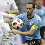 Uruguay's Diego Godin in action with France's Antoine Griezmann.