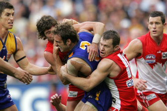 Chris Judd is tackled by Paul Williams and Brett Kirk in the 2005 decider.