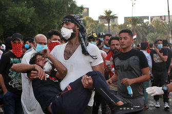 An injured protester is rushed to a hospital during a demonstration in Baghdad, Iraq, on Saturday. Protesters converged on a central square as security forces erected blast walls to prevent them from reaching a heavily fortified government area after a day of violence that killed scores.