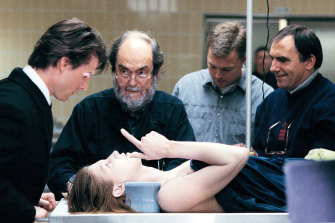 Stanley Kubrick and Tom Cruise (left), with Julienne Davis as the corpse and director of photography Larry Smith (right) on the set of Eyes Wide Shut.