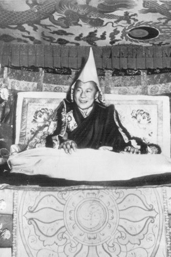 The Dalai Lama, aged 15, smiles from his throne in Lhasa in 1950.