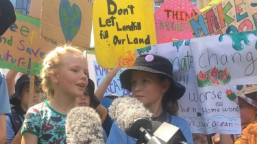 Thea, 8, and Elia Reid, 11, front the media pack at the Brisbane rally for climate change.