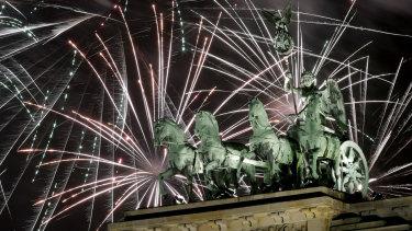 Fireworks light the sky above the Quadriga at the Brandenburg Gate.
