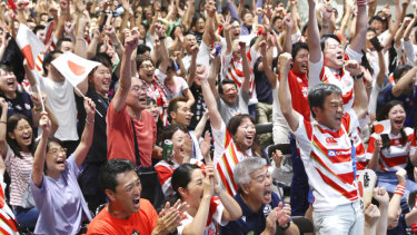 Supporters at a public-viewing event celebrate as Japan score a try against Ireland.